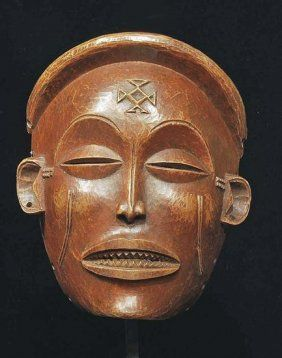 "An African Chokwe Wood Carved Mask Pwo, Zaire    Lovely carved mask with grinning mouth, delicate almond shaped eyes, arched brows, and scarification markings on cheeks, forehead, and temples. Reddish brown patina. 6-1/2""H, complete with custom mount. Depicting a female ancestor which gives the fertility to the audience.    Provenance: Ex Sebastian Fernandez"