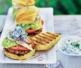 Lamb burger topped with lettuce, tomato and tzatziki in a bun