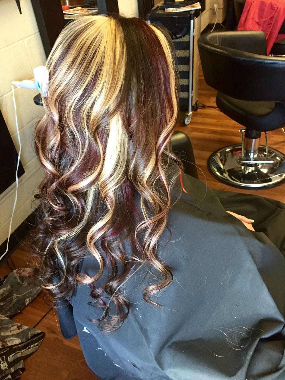 Dark brown with red violet and blonde chunky highlights.