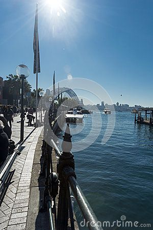 Clear blue winter sky at Circular Quay with the harbour bridge in the background and people enjoying the foreshore, Performers entertaining the people. Copy space.