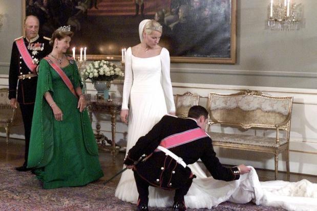 Un novio solicito, arregla el velo y la cola del vestido antes de las fotos oficiales