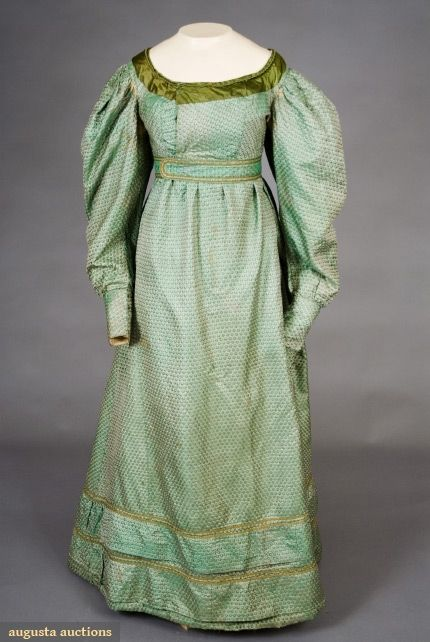 Green silk apron front gown, 1820's  The Tasha Tudor Historic Costume Collection - Augusta Auctions  Woven brocade with stylized floral pattern, neckline trimmed with olive green satin and cord, padded rouleau hem