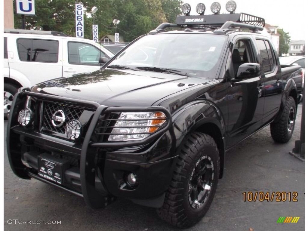medium resolution of black nissan frontier with brush guard and wilderness roof rack
