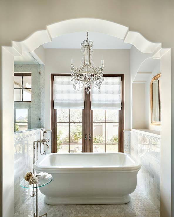 An Arched Doorway Leads To An Ethereal Bathroom Nook Filled With A Freestanding Bathtub And A V Elegant Bathroom Design Elegant Bathroom Mediterranean Bathroom
