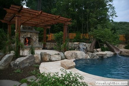 Pergola raised patio fireplace pool with waterslide for Fireplace on raised deck