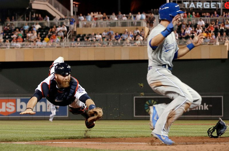 Minnesota Twins catcher Ryan Doumit, left, makes a futile dive as Kansas City Royals' David Lough runs by to score on a bunt single by Jarrod Dyson in the eighth inning of a baseball game, Tuesday, Aug. 27, 2013 in Minneapolis. The Royals won 6-1. (AP Photo/Jim Mone)