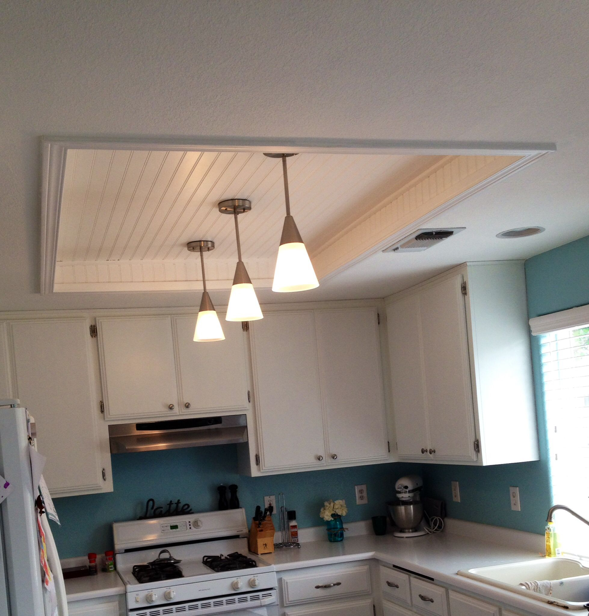 Ugly fluorescent lightgone replaced with beadbord trim and kitchen fluorescent light box remodel with wood beadboard ceiling panels in white paint finishes also stainless steel pendant lighting fixtures mozeypictures Choice Image