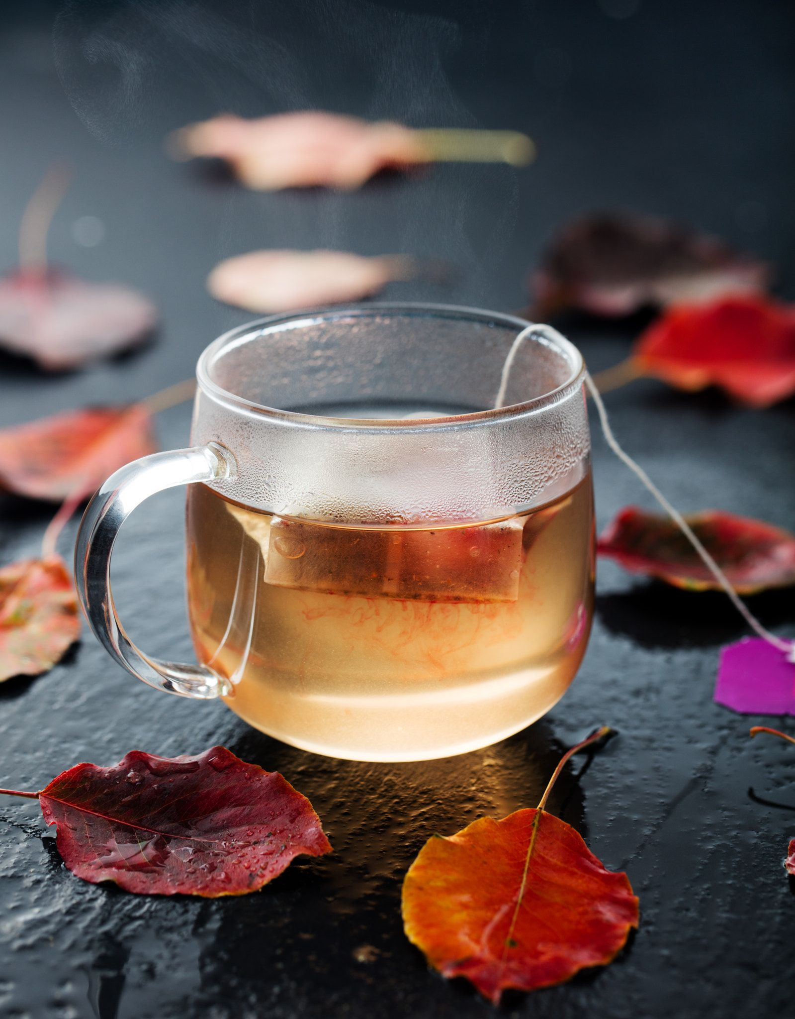 Cup of herbal and fruit tea with autumn leaves  Cup of tea with