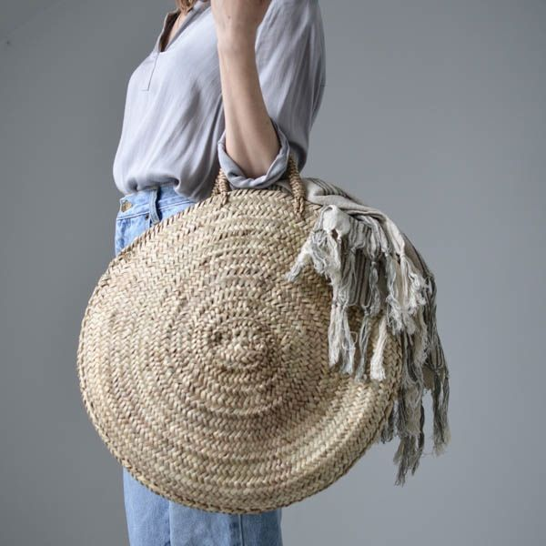 "The perfect Boho-chic bag. This rustic basket is handmade using dried palm leaves and features a woven handle. Approximately 18"" diameter…"
