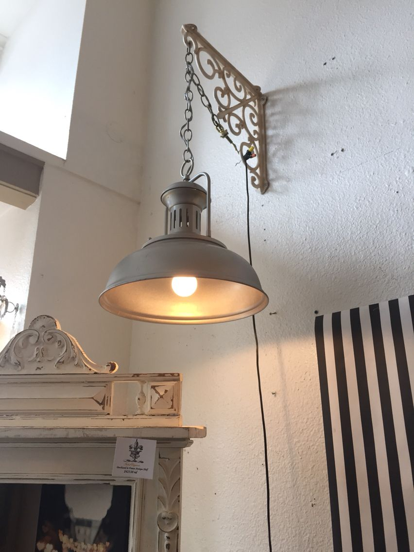 I love this idea of hanging a pendant light off a wrought iron