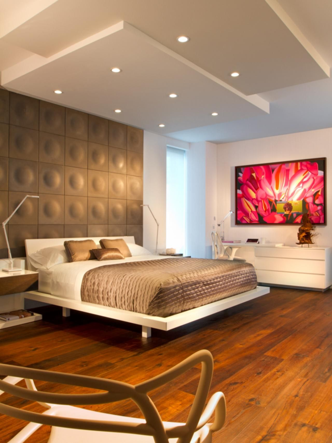 "When designing this cool, contemporary bedroom, designer Jay Britto was inspired by his clients' love of loft-style architecture. ""We wanted to give the space a New York feel,"" he says. ""We achieved this by opening up the living area to expand the space, and by incorporating industrial-style materials like the polished concrete panels that form the headboard."""