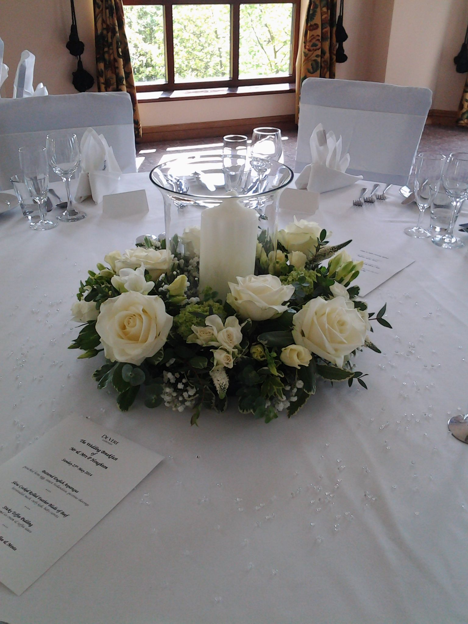 wedding reception table decoration made using fresh flowers and foliage with hurricane lamp and