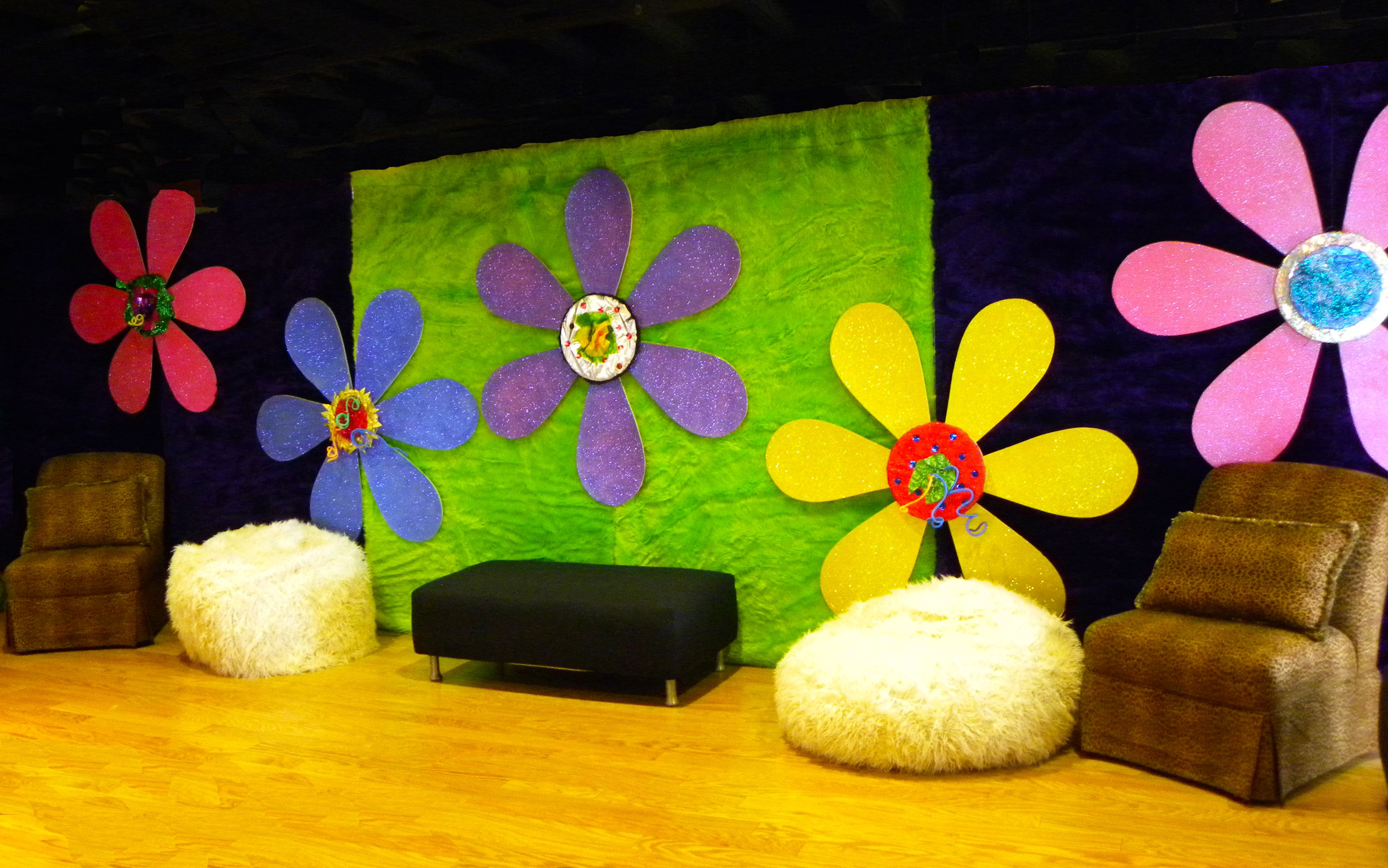 Groovy flower backdrop with retro seating party theme 70s shag decor eventuresinc
