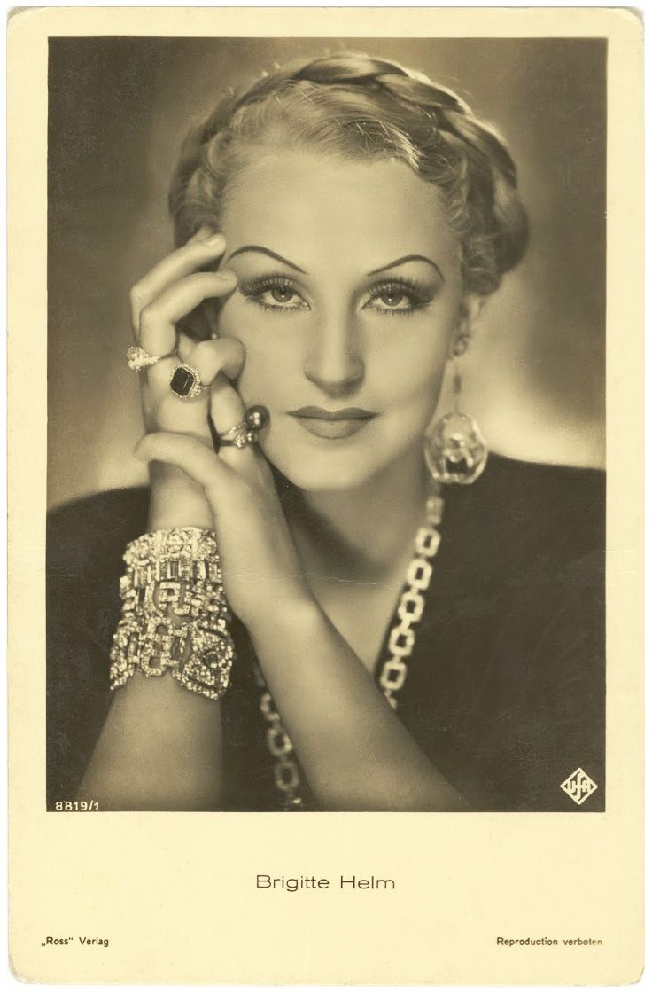 "Brigitte Helm (1906-1996) was a German actress best remembered for her dual role as Maria and her double, the Maschinenmensch, in Fritz Lang's 1927 film METROPOLIS. She incurred Nazi wrath for ""race defilement"" by marrying Dr. Hugo von Kuenheim, an industrialist of Jewish descent. Upon the expiration of her contract with UFA, she moved to Switzerland, where she later had four children. Helm was considered for the title role in BRIDE OF FRANKENSTEIN before Elsa Lanchester was given the part."