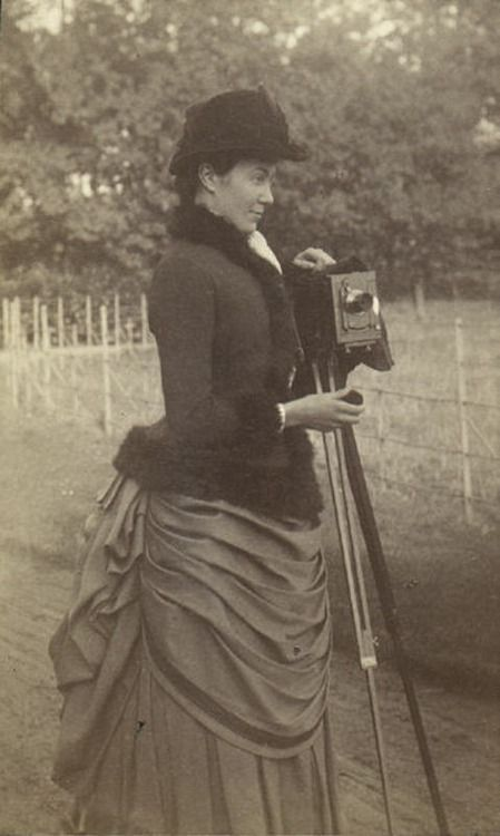 Woman taking a photograph (1880s). Notice the multiple folds on the apron; it is fuller than most patterns out there today.