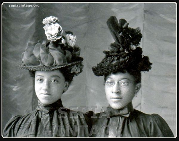 Two well dressed women wearing amazing hats, late 1800's.