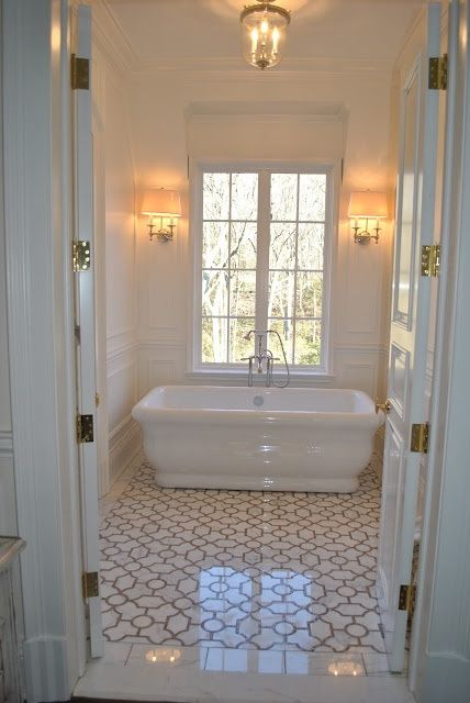 a neutral white and gray bathroom featuring a deep ceramic bathtub and white and gray patterned tile floors unique bathroom ideas u0026 decor
