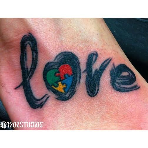 Adorable touching love lettering with autism awareness heart female foot tattoo by Sailor B.