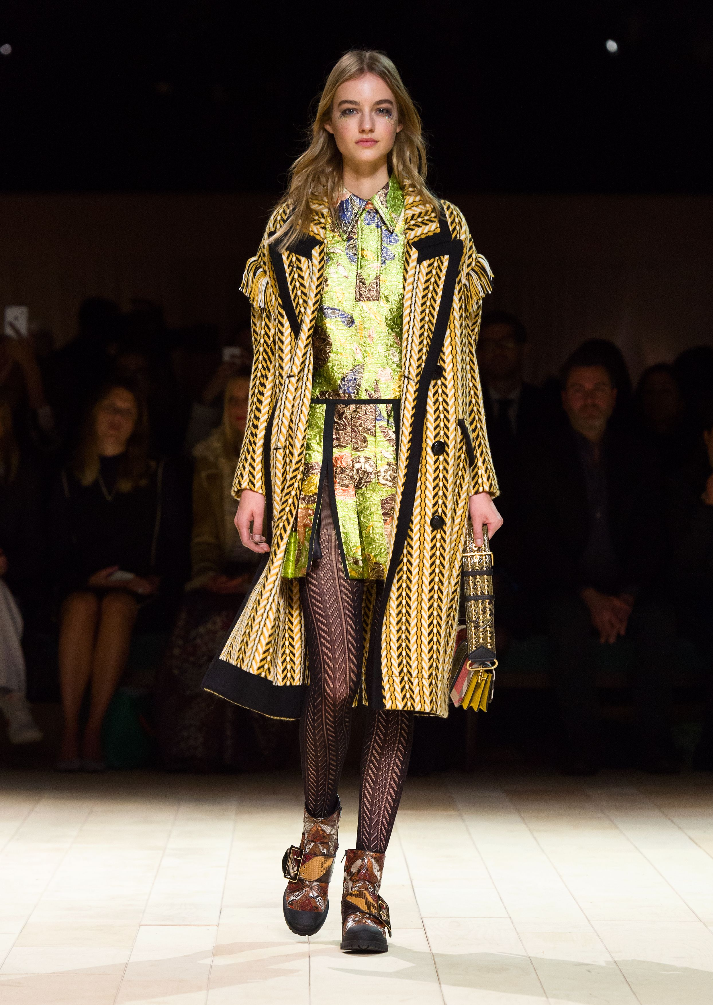 The Fringe Coat in ochre yellow herringbone wool silk, worn over a jacquard dress and styled with The Patchwork bag and The Buckle Boot. Discover the collection at Burberry.com
