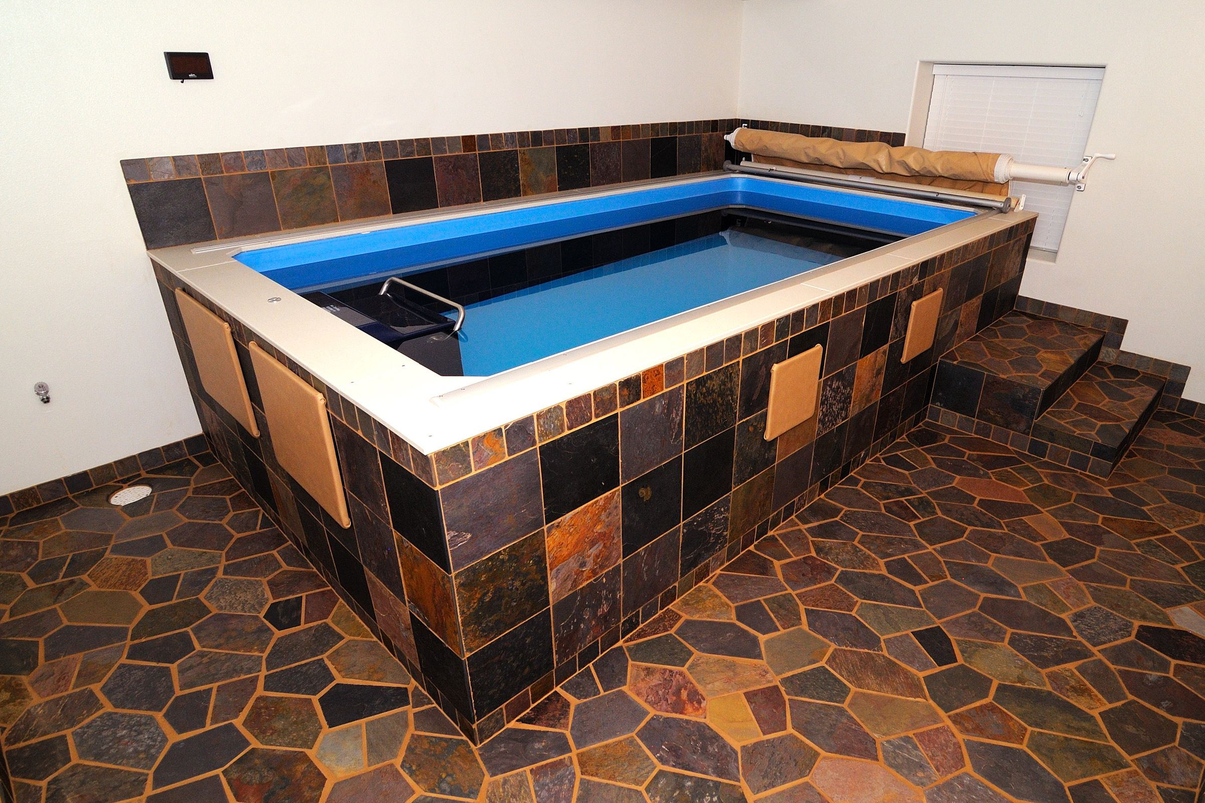 A Basement Transformed With An Endless Pool Skirted And Surrounded By Rich Onyx And Earth Tone Tiles In Geometric Patterns With I Endless Pool Swim Spa Pool
