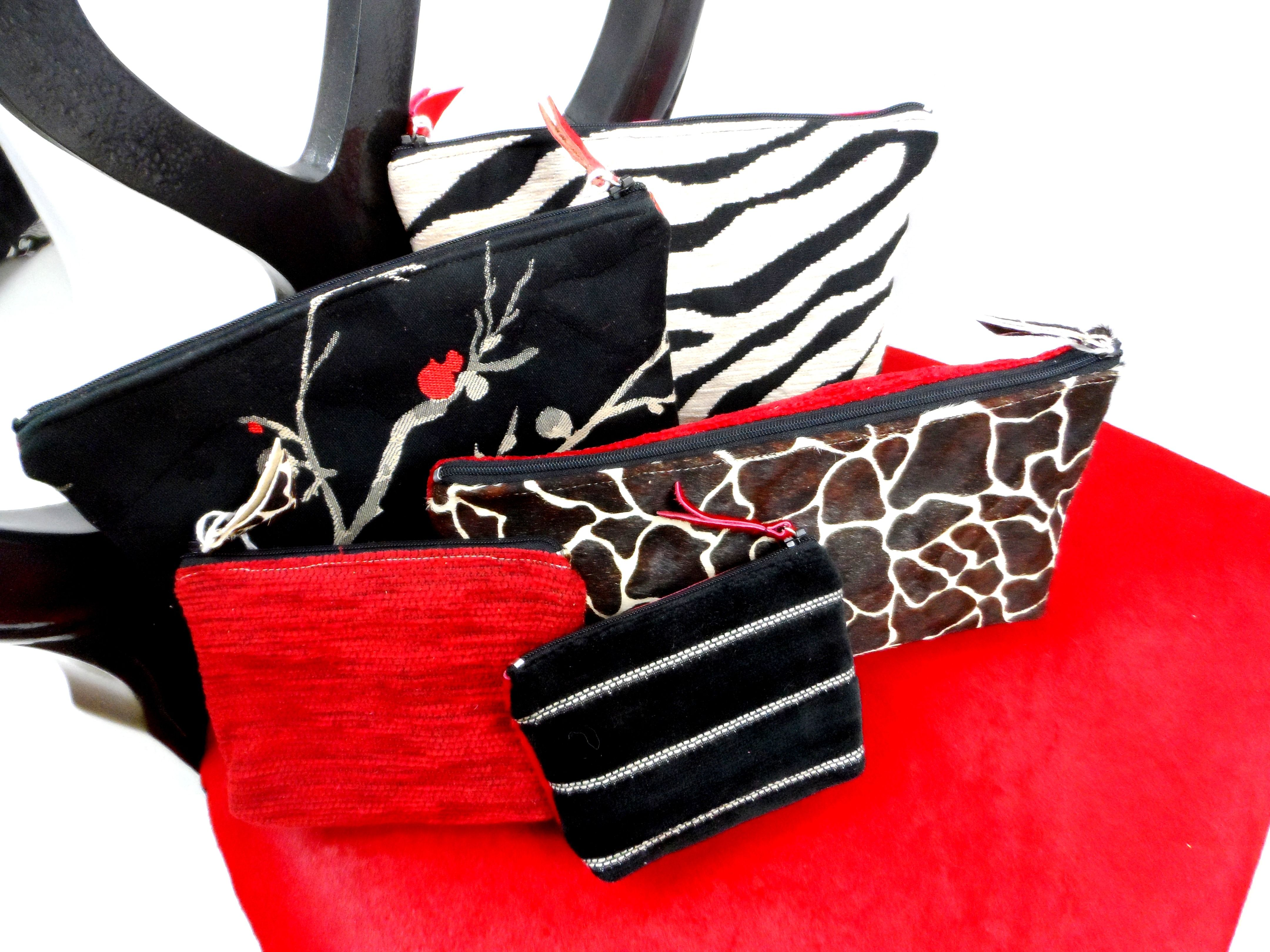 A gorgeous purse collection sitting on an equally gorgeous chair covered in brilliant red ponyskin. Digitally printed leathers, silk linings, everything lovely! Available.