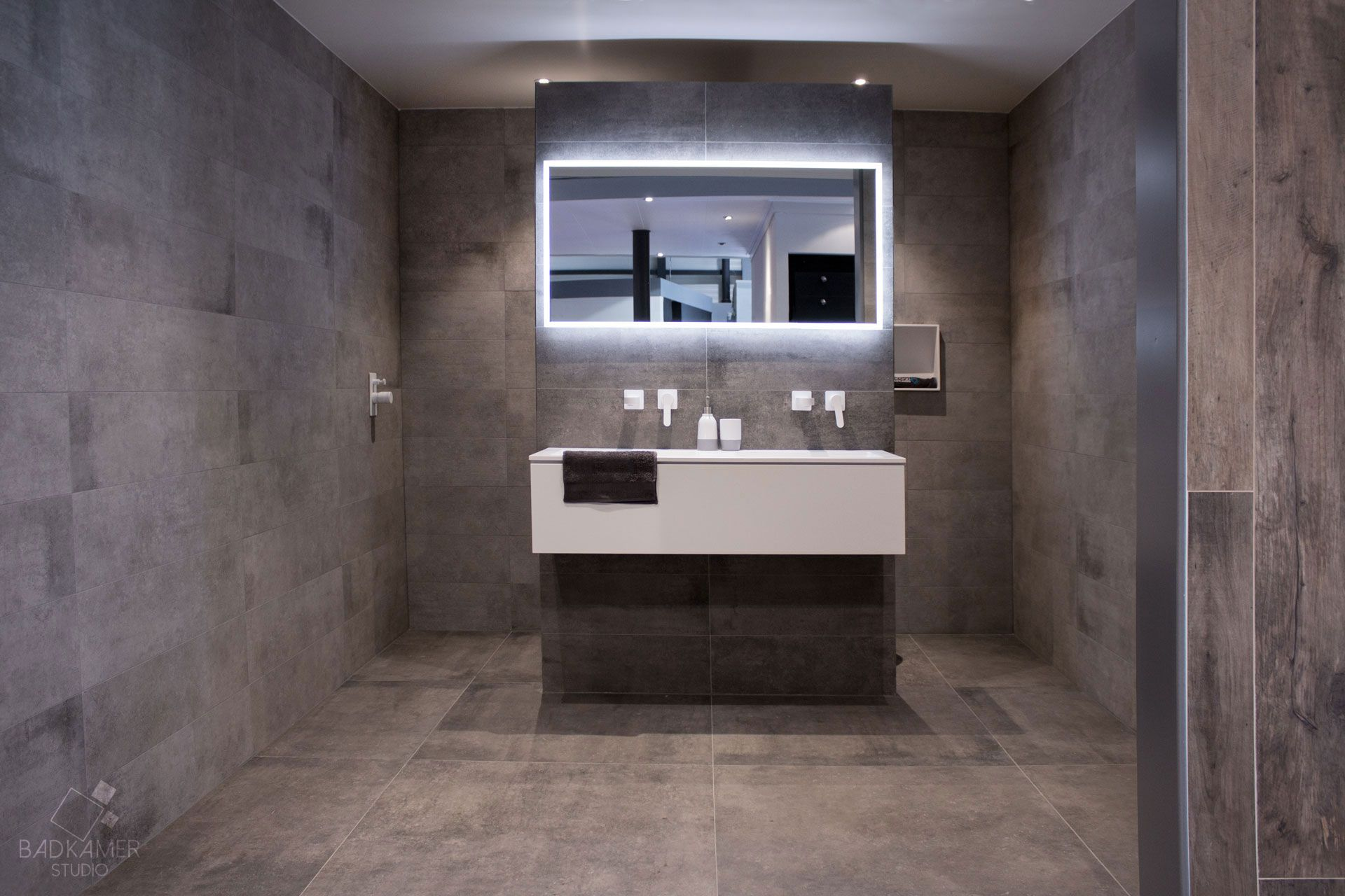 maatwerk badkamer met overall grijze look mat witte kranen en een