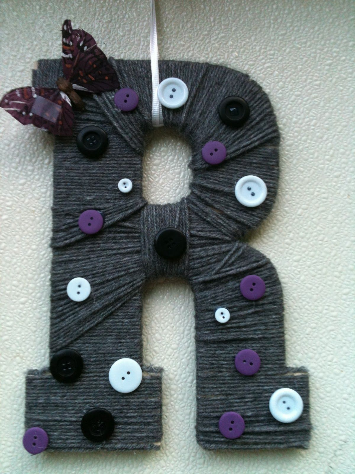 It's a yarn covered letter, no it's a button covered letter....ok, so it's a yarn/button covered letter :)