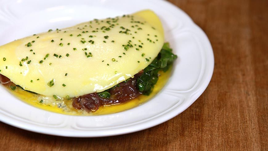 Recipe for Omelet 'Du Jour' from Au Cheval. Continuous stirring creates a silky texture, and the brief cooking time results in an even, pale yellow complexion.