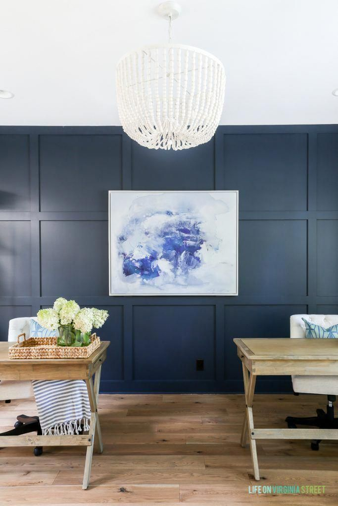 Home office with Benjamin Moore Hale Navy board and batten wall, navy blue and white abstract artwork, whitewashed bead chandelier, wood desks and Mannington white oak Maison Normandy Bistro hardwood floors. #boardandbattenwall