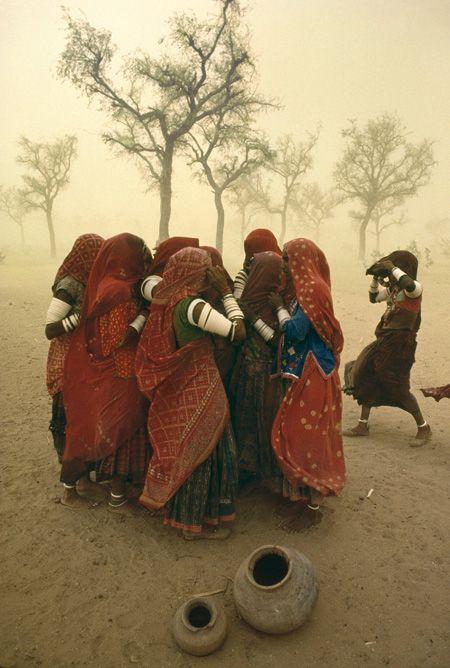 Le donne si stringono per proteggersi da una tempesta di sabbia in India, 1984