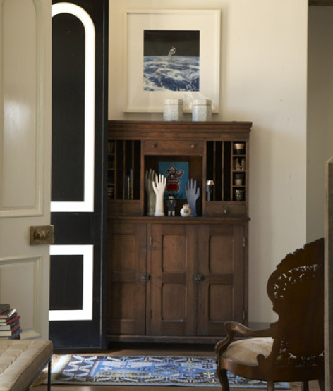 An antique mail-sorting cabinet in the entry of a California home holds glove molds, painted wood figurines from Moss, John Derian canisters, and vintage clay vessels; the leather-upholstered bench is by Oly, and the rug is from Pottery Barn Teen.
