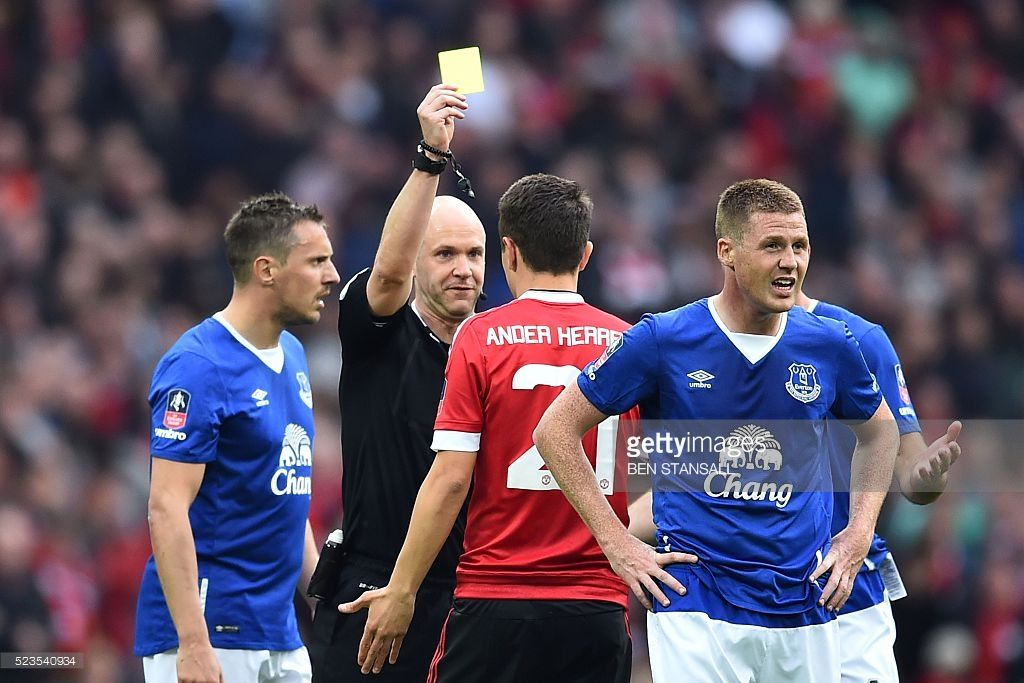 Manchester United's Spanish midfielder Ander Herrera (3L) is shown a yellow card by referee Anthony Taylor (2L) after fouling Everton's English midfielder Ross Barkley during the English FA Cup semi-final football match between Everton and Manchester United at Wembley Stadium in London on April 23, 2016. / AFP / BEN