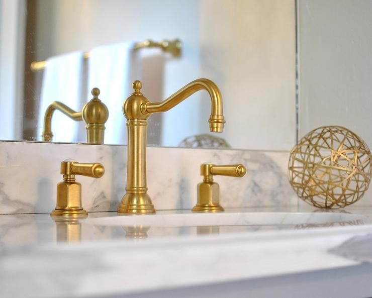 Glam bathroom features a washstand with topped with honed gray and ...