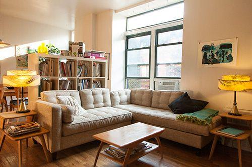 Dividing An Open Room With Sectional Sofas And A Bookshelf Via Design Sponge
