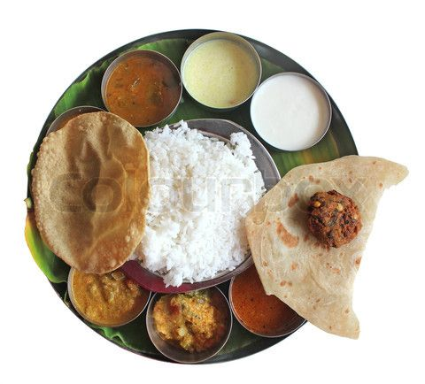 Traditional southern indian plate meals on banana leaf isolated on white. Traditional vegetarian wholesome indian food with variety of curries, rasam, sambar, rice and chapatti.