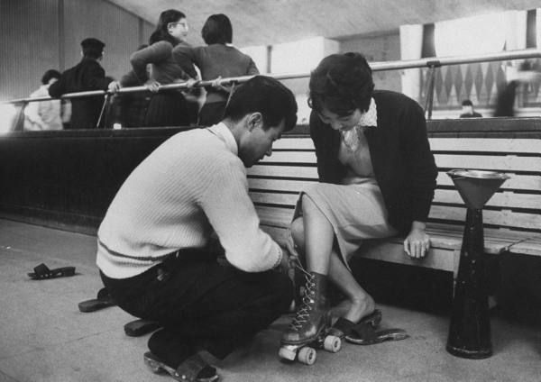 Young Japanese couple helping his date into her skating kit. Tokyo, 1959.