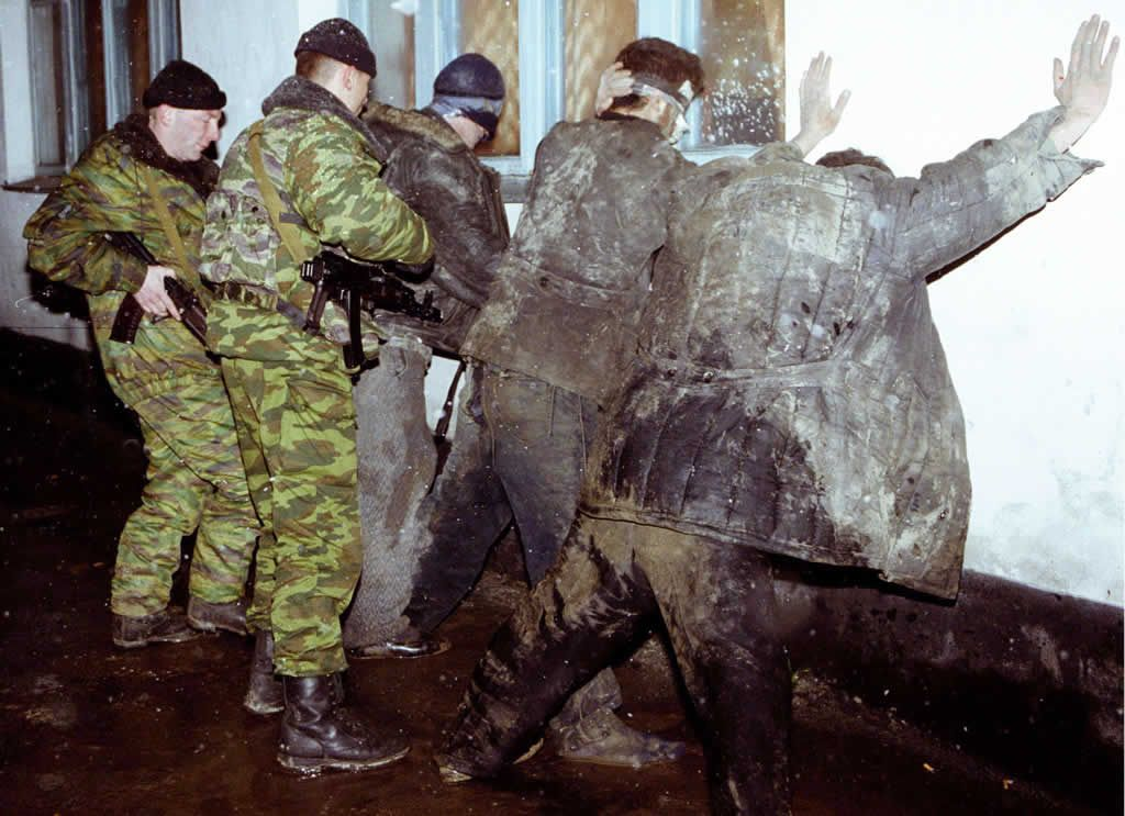 Chechnya. Chernokozovo. February 2000. Russian soldiers inspect Chechen men standing along a wall in the prison of the Chechen village. Photograph: Alexander Nemenov/EPA