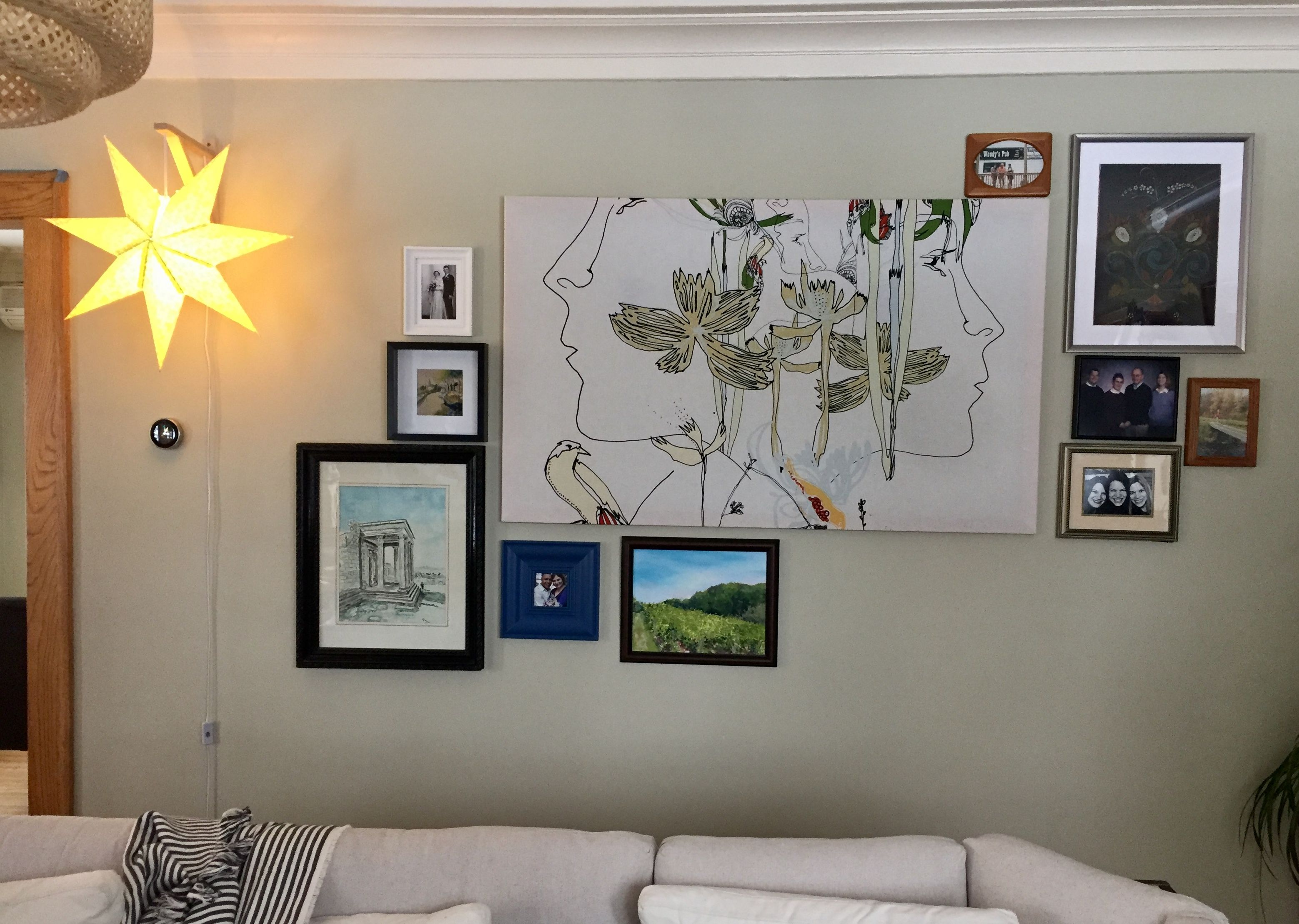 Gallery wall adds depth for floating living room area long and