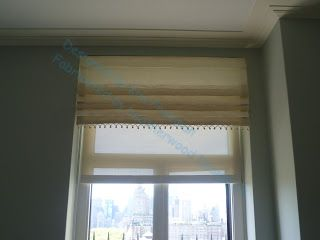 Faux Roman valance, with roller shade underneath.  Consider for bathroom