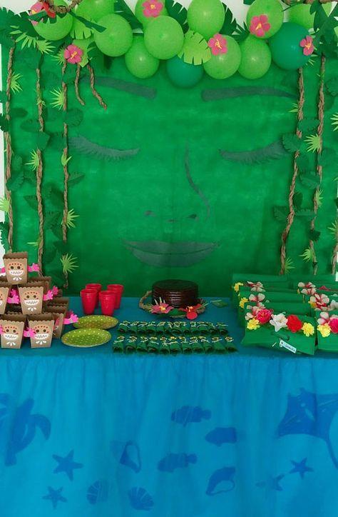 Cumpleaños Moana para hacer tú mismo. Incluye el arte y las instrucciones para armar el fondo con la cara de Te Fiti, caja de snacks de kakamoras, bandeja para hot dogs con forma de bote y animales del océano para decorar la mesa principal.