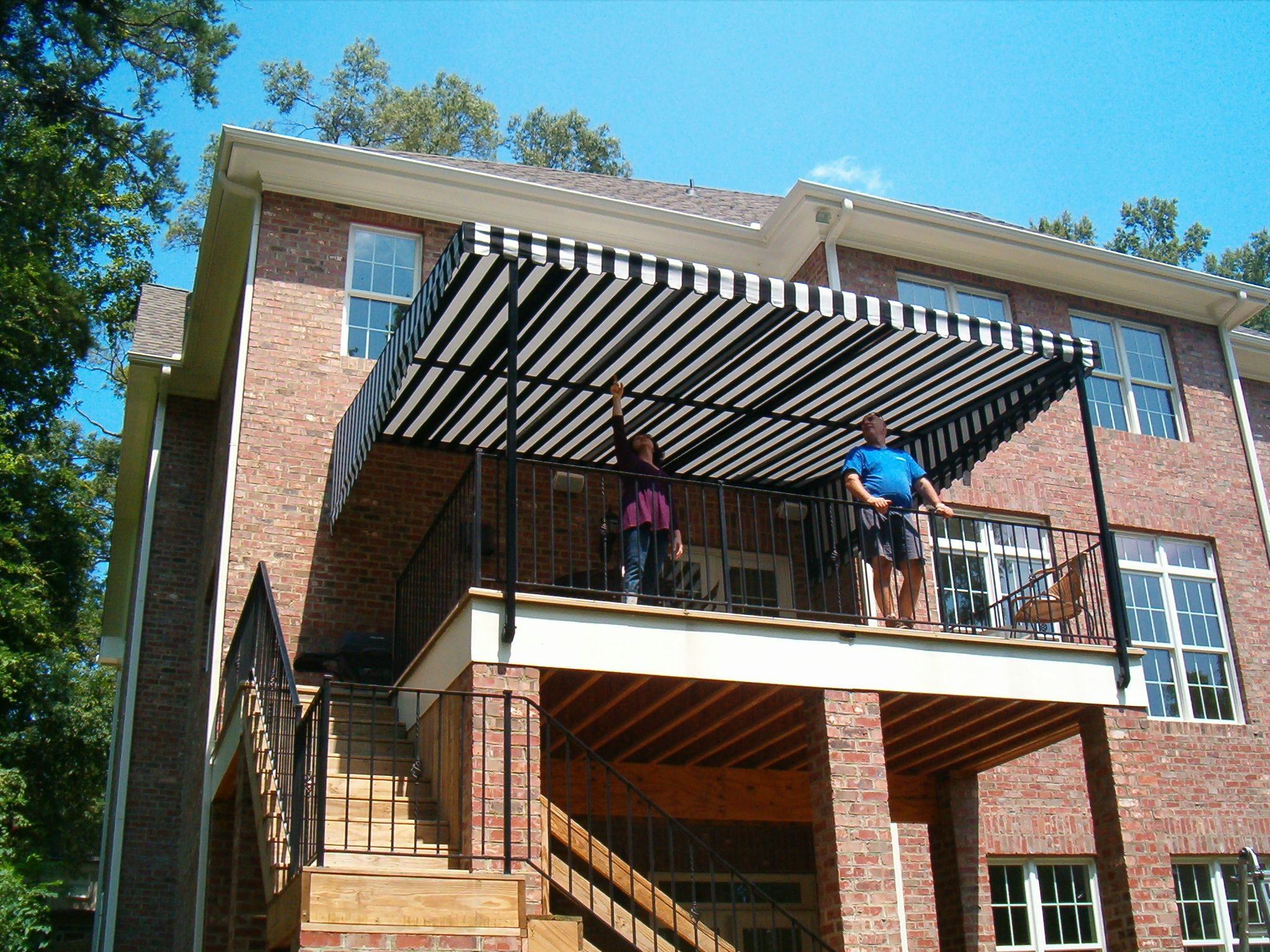 happy alpha customers surveying their new stationary deck awning