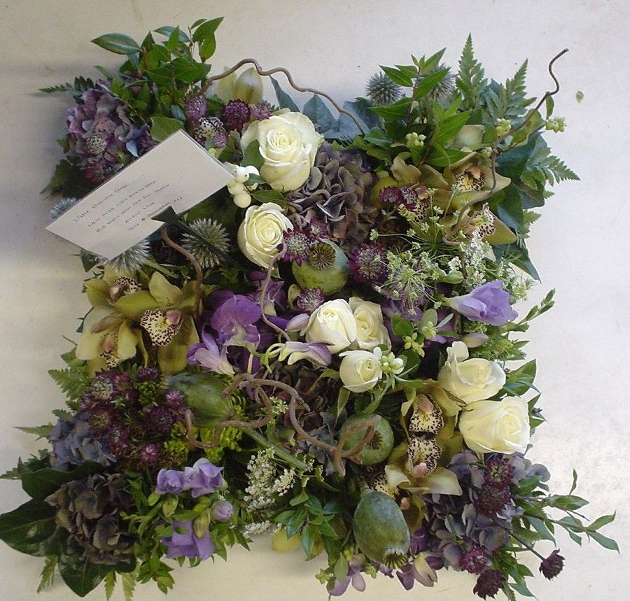 Funeral, sympathy pillow arrangement with purple freesia and poppy pods