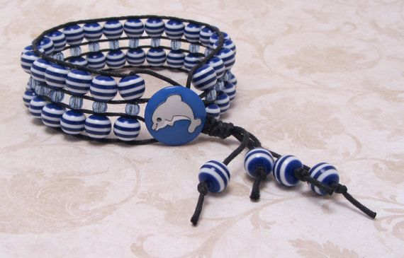 Blue Buoy Blue Striped Cuff Bracelet w/adorable Dolphin Button  Really cute blue striped cuff with baby blue glass beads down the middle. This cuff would be perfect for Spring or Summer with a cute dress or white shorts. These resin beads remind me of toys I have seen in the dolphin pens and that is why I topped it off with an adorable dolphin button!    Fits up to a 7.5'' wrist.    $18.00