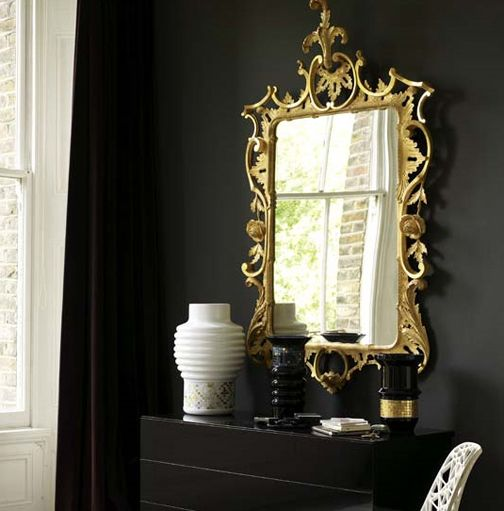 there's always a place for dramatic metallic pieces such as this stunning mirror, which is brought into splendid relief against the black walls.