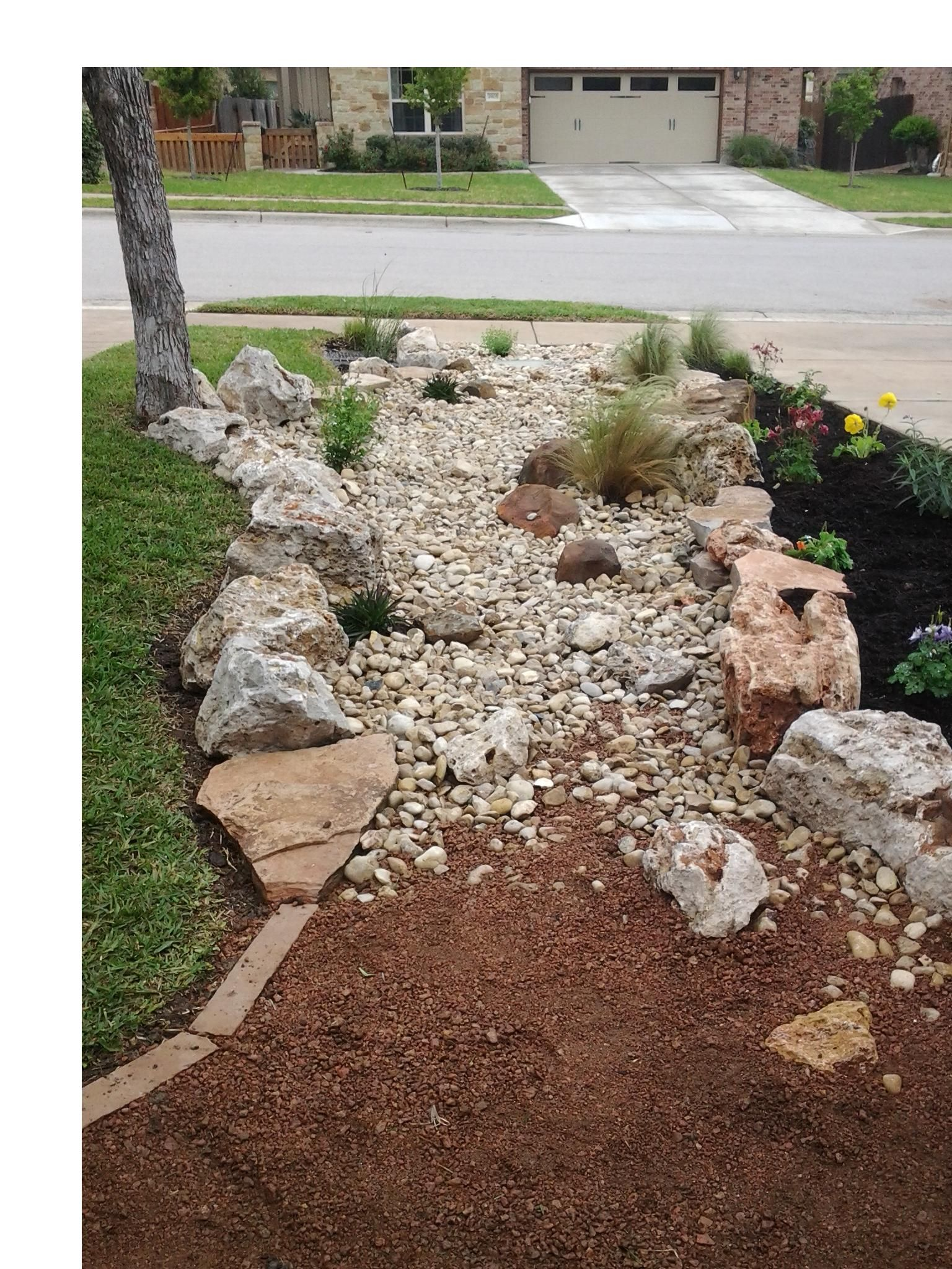 Dry creek bed between two houses with a decomposed granite wash