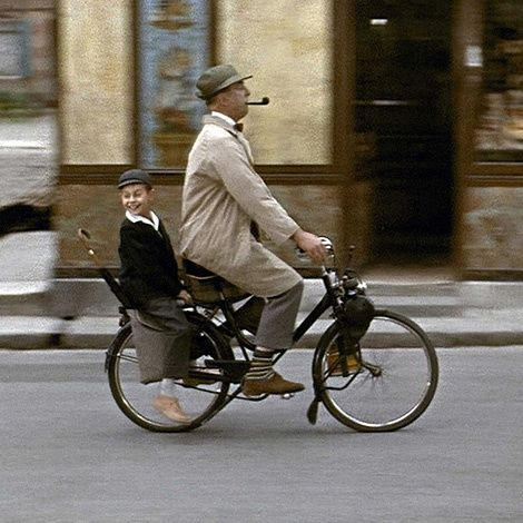 Father taking his son to work on his bicycle .