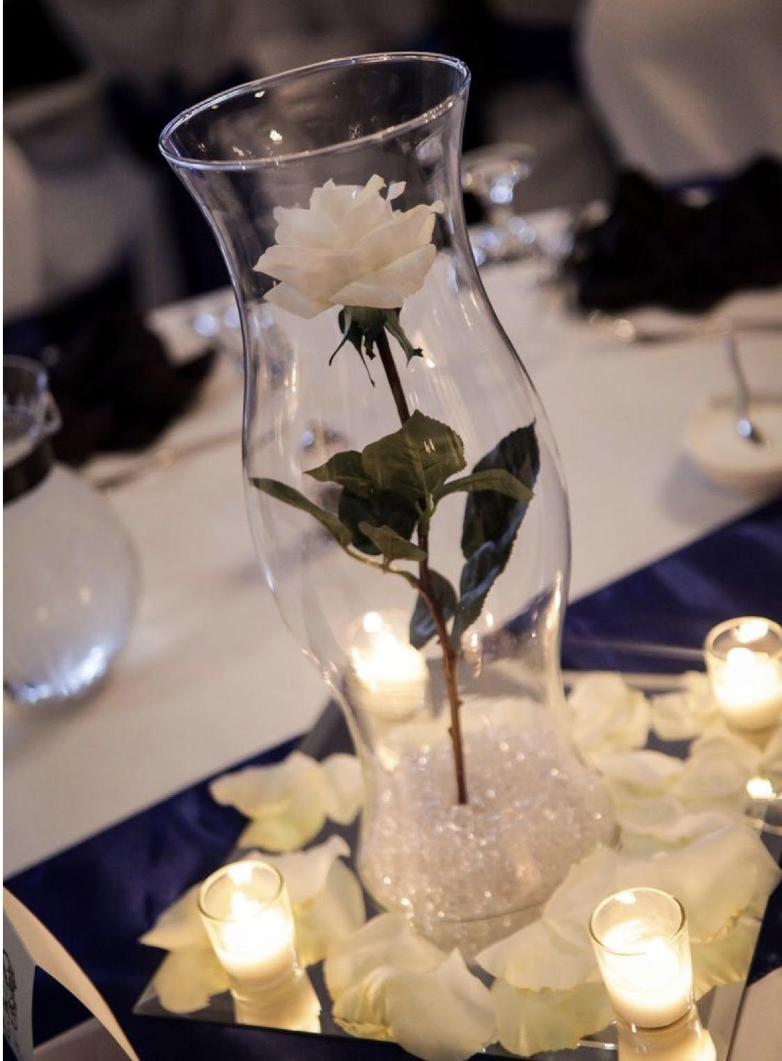 Pin by courtney chase on wedding pinterest centerpieces single white long stem rose 16 inch hurricane vase royal blue sash and a few fresh white rose petals and some candles reviewsmspy