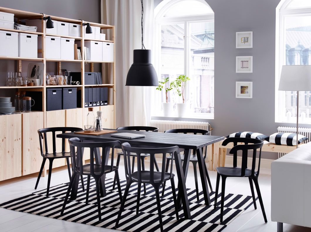 a large dining room with a black dining table and six chairs combined with storage in solid pine