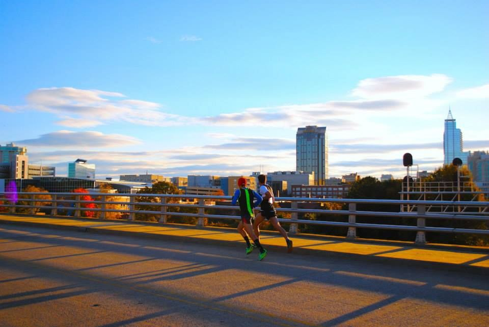 Jordan Zwick (left) heads for home in the City of Oaks Half Marathon with the beautiful Raleigh skyline in the background.  Shoes: Salming Race