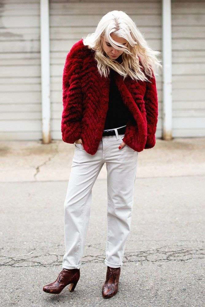A red coat is paired with white jeans and boots